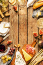Different kinds of cheeses wine baguettes fruits and snacks on rustic wooden table from above french tasting party or feast Royalty Free Stock Photo
