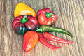 Different kinds of sweet and hot chili peppers on grunge backgro Royalty Free Stock Photo