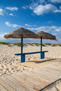 Different parasols and sun loungers on the empty beach on tavira island algarve portugal Royalty Free Stock Photography