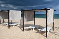 Different parasols and sun loungers on the empty beach tavira island before storm algarve portugal Stock Images
