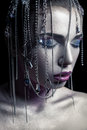Different style of beauty. young beautiful fashion model with silver, purple, blue makeup and shiny silver jewelry chain on her fa Royalty Free Stock Photo