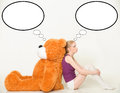 Different thoughts young blond woman with a big teddy bear sitting on the floor with his back to each other Stock Photography