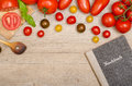 Different tomatoes with wooden spoon and recipe book on a old board Stock Photos