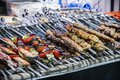 Different types of barbecue meat and fish on skewers
