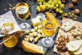 Different types of cheese on board, olive, fruits, almond and wine glasses on stone table Royalty Free Stock Photo