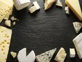 Different types of cheeses arranged as a frame on black board Stock Image