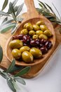 Different types of olives green and black on wooden plate on white table. Close-up Royalty Free Stock Photo
