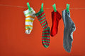 Different types of striped socks hanging isolated on red pair a rope background Stock Photos