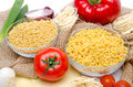 Different types of uncooked pasta and vegetables on a burlap isolated white Stock Image