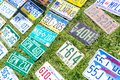 Different USA car retro license plates at flea market. Vintage vehicles registration numbers lay on grass at swap meet Royalty Free Stock Photo