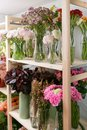 Fresh spring flowers in refrigerator for flowers in flower shop. Bouquets on shelf, florist business. Royalty Free Stock Photo