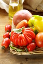 Different varieties of tomato with basil on a wooden table Stock Photography