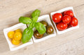 Different wet tomatoes with basil in bowls Stock Photos