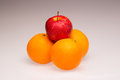 Differentiation oranges and a red apple as a symbol and concept for and competition Stock Image