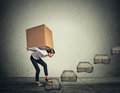Difficult task concept. Woman carrying heavy box upstairs Royalty Free Stock Photo