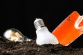Dig idea light bulb as symbol in soil with shovel to Royalty Free Stock Photo