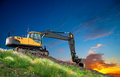 Digger at sunset on hill with grass and flowers Royalty Free Stock Images