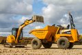 A digger tipping soil into a site dumper truck Royalty Free Stock Photo