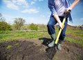Digging in the garden image of male farmer rubber boots didgging Stock Photography