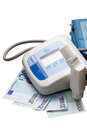 Digital blood pressure monitor and the euro cash isolated on white background Stock Photos