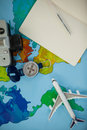 Digital camera, dairy, pen, map, compass and airplane model on table Royalty Free Stock Photo