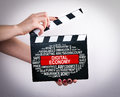 Digital Economy Concept. Female hands holding movie clapper Royalty Free Stock Photo
