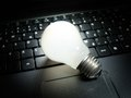 Digital ideas light bulb that is lit on your computer keyboard as symbol of new in computing and electronics Royalty Free Stock Images