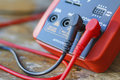 Digital multimeter with connected probes on a wooden table Royalty Free Stock Photo