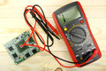 Digital multimeter with probes on a wooden table Royalty Free Stock Photo
