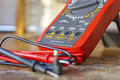 Digital multimeter with probes on a wooden table in the workshop Royalty Free Stock Photo