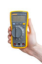 Digital multimeter in technicians hand Stock Photo