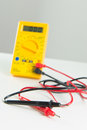 Digital multimeter yellow for testing electronic circuits Stock Images