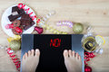 Digital scales with female feet on them and sign `no!` surrounded by christmas decorations and unhealthy food. Royalty Free Stock Photo