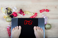 Digital scales with female feet on them and sign `omg!` surrounded by Christmas decorations Royalty Free Stock Photo