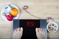 Digital scales with female feet on them and sign `yes!` surrounded by healthy food. Royalty Free Stock Photo