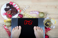 Digital scales with woman feet on them and sign sign`OMG!` surrounded by christmas decorations and unhealthy food Royalty Free Stock Photo