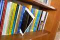 Digital tablet book shelves with physics books in the library with ipad mini in front of the books Royalty Free Stock Images