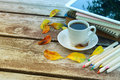 Digital tablet, books, colorfull pencils and cup of coffee on old wooden table outdoor in the park. Royalty Free Stock Photo