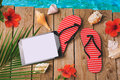 Digital tablet, flip flops and hibiscus flowers on wooden background. Summer holiday vacation concept. View from above Royalty Free Stock Photo