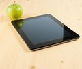 Digital tablet pc near green apple on wood table Stock Photography