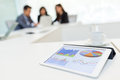 Digital tablet showing graph with business partners discussing i Royalty Free Stock Photo