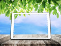 Digital tablet on wooden table with green leaves and blue sky background