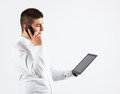 Digitized human interaction young man is interacting with business partners using his wireless devices mobile phone and tablet Stock Photography