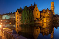 Dijver canal in bruges belgium the with its historical buildings and the belfry or belfort tower reflected on the waters at night Stock Photo
