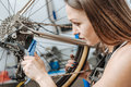 Diligent female technician brushing the chain of the bicycle Royalty Free Stock Photo
