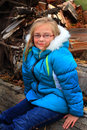 Dimples hoody and wood pile a smile on a cute little blond year old girl wearing glasses a warm blue winter coat sitting on a Royalty Free Stock Image