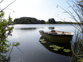 Dinghy on lake in denmark in summer with water lilies and reeds Stock Images