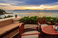 Dining romance sea view table on balcony with and sunset on the beach Royalty Free Stock Photos