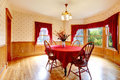 Dining room in old house interior with wooden wall trim and wallpaper table with bright red table cover which blend perfeclty with Stock Photo