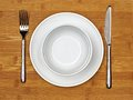 Dining set bowl and plate with fork and knife on a bamboo wood background Royalty Free Stock Images